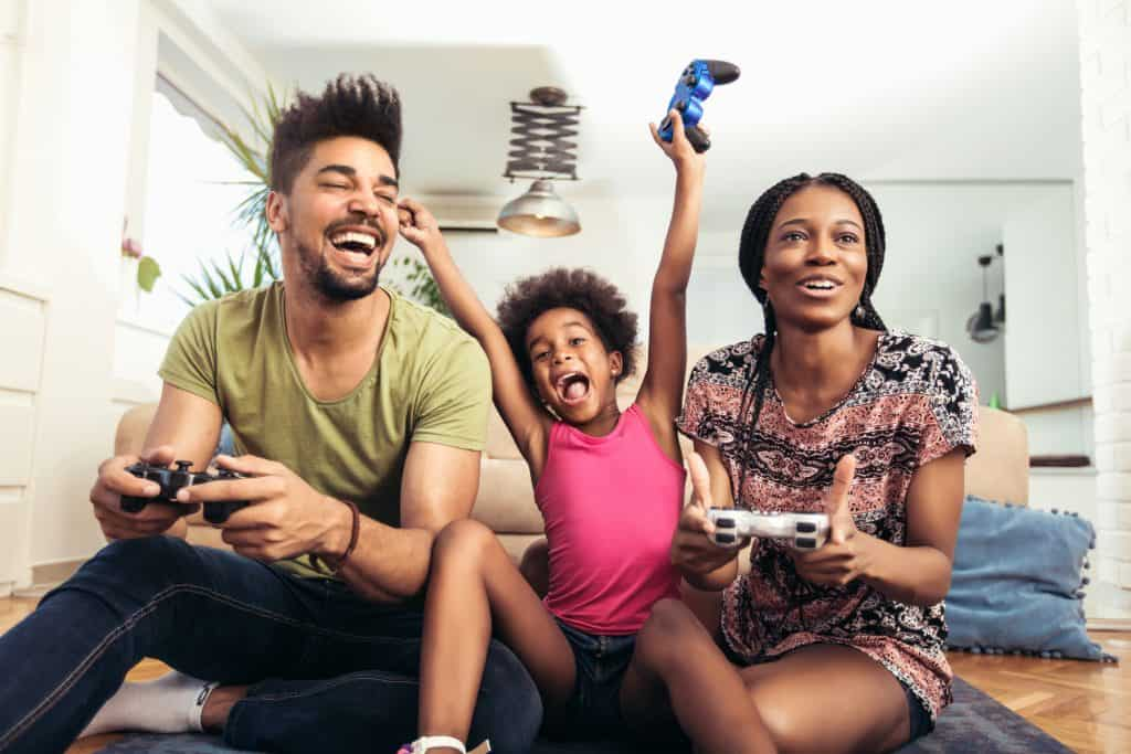 Smiling Family Sitting On The Couch Together Playing Video Games